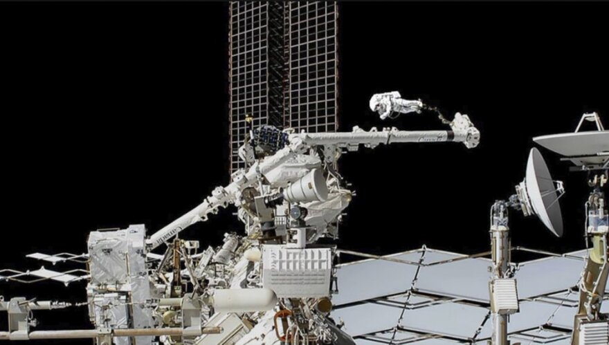 Astronauts work on cosmic ray detector