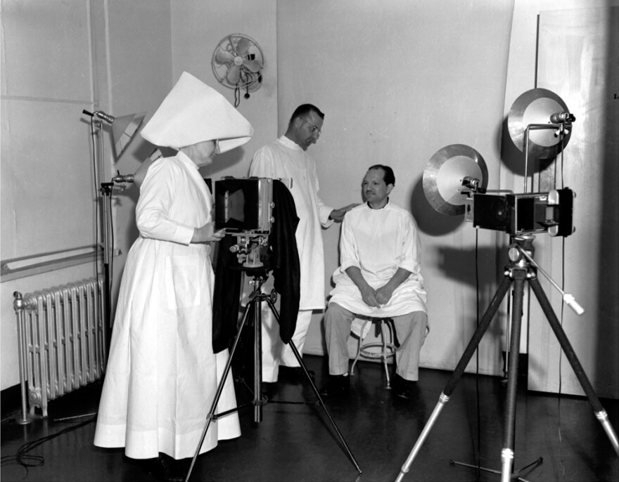 Sister Hilary Ross takes photos documenting a patient's treatment progress in the infirmary at the leprosarium in Carville, circa 1950. The photo was taken by Johnny Harmon, a patient with leprosy, for <em>The Star</em><em>, </em>a magazine for the residents at Carville.