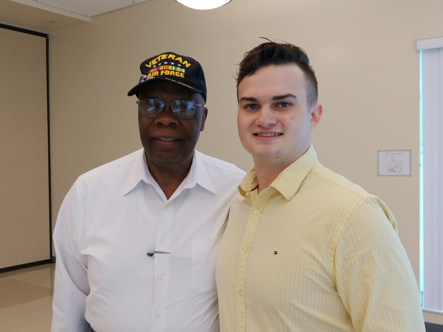 Older African American man and younger white man pose for a photo