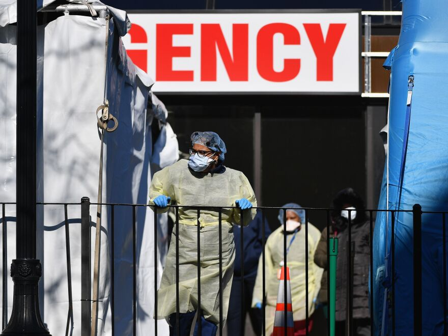Medical workers are seen outside Elmhurst Hospital Center in the Queens borough of New York City on Thursday. Thirteen people with the virus died at the hospital in a 24-hour span the day earlier.
