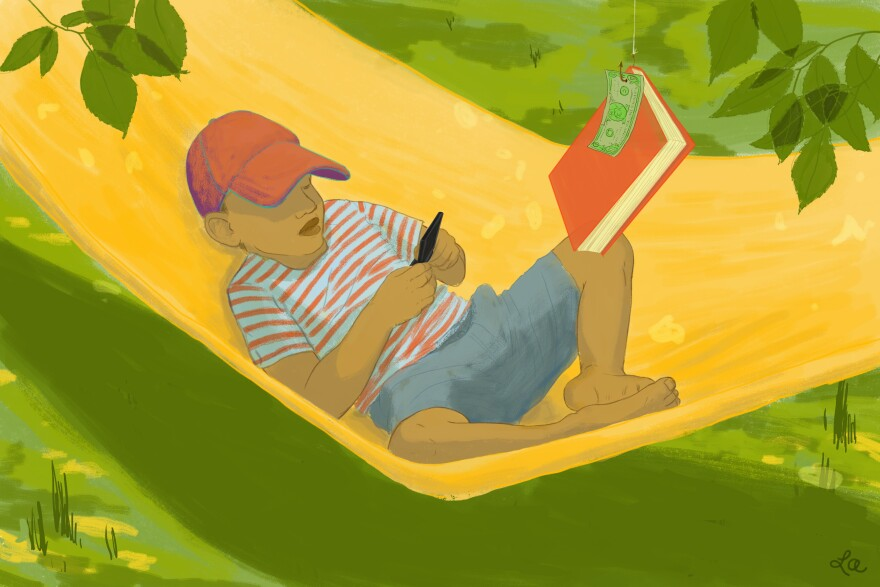 Young boy in hammock playing video game while a book with a dollar attached hangs in front of him.