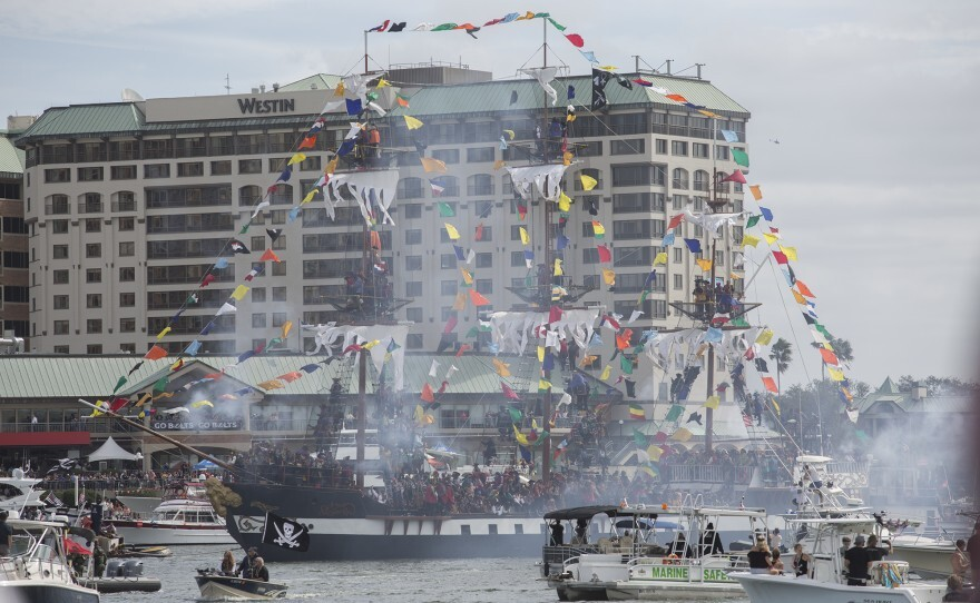 A pirate ship decorated with multi colored flags sails on the Hillsborough River in a cloud of canon smoke.