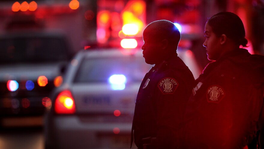 Emergency personnel stand Tuesday night at a kosher supermarket, which shooters targeted in a deadly attack hours earlier in Jersey City, N.J.