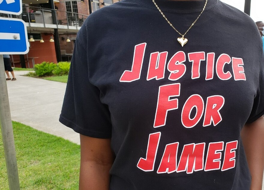 "A Black woman wears a black t-shirt with red and white lettering that says, ""Justice for Jamee"""