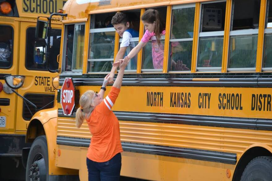Children reach their hands out from a North Kansas City School District Bus