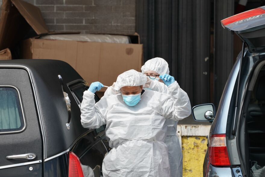 Funeral home workers put on protective gear to retrieve a body from a refrigerated truck outside a Brooklyn hospital in early April. As of Sunday, the U.S. reported the most coronavirus deaths in the world, surpassing Italy.