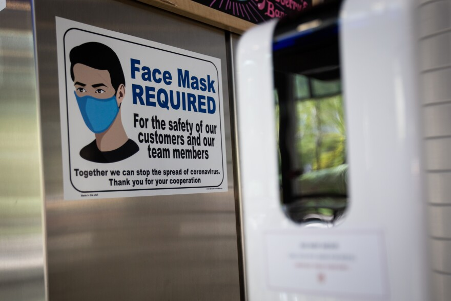 Hand sanitizing stations and signs encouraging people to wear masks are placed around the UT Austin campus.