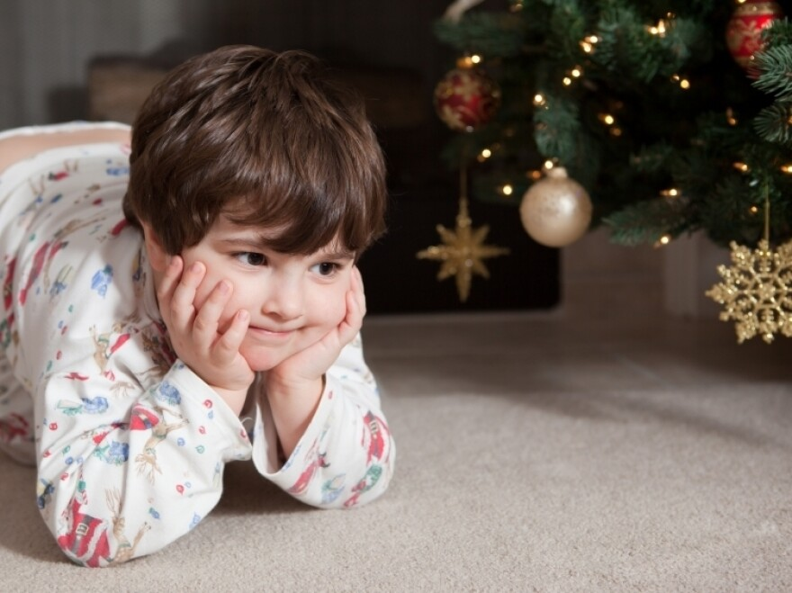 A child sits in anticipation near a Christmas tree
