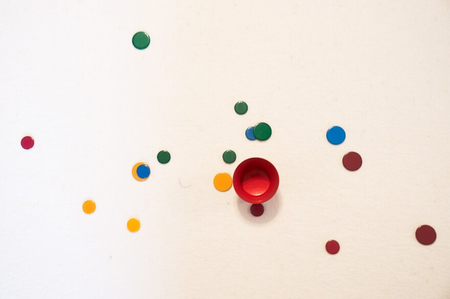"""A tiddlywinks game mid-play, with winks spread out around the pot. Though players eventually want to """"pot"""" their """"winks,"""" players also strategize how to block their opponents by landing their piece on top of another's piece."""