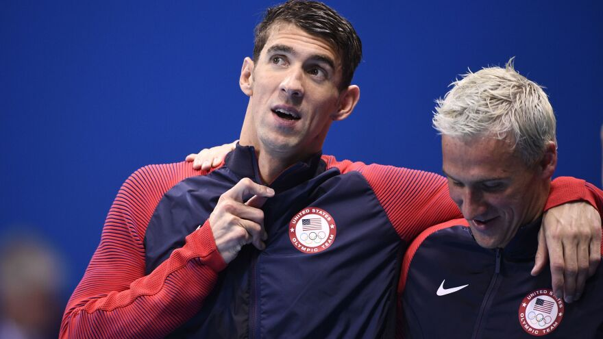 Michael Phelps (left) and Ryan Lochte celebrate on the podium after winning the men's 4x200-meter freestyle relay final earlier in the Rio Olympics.