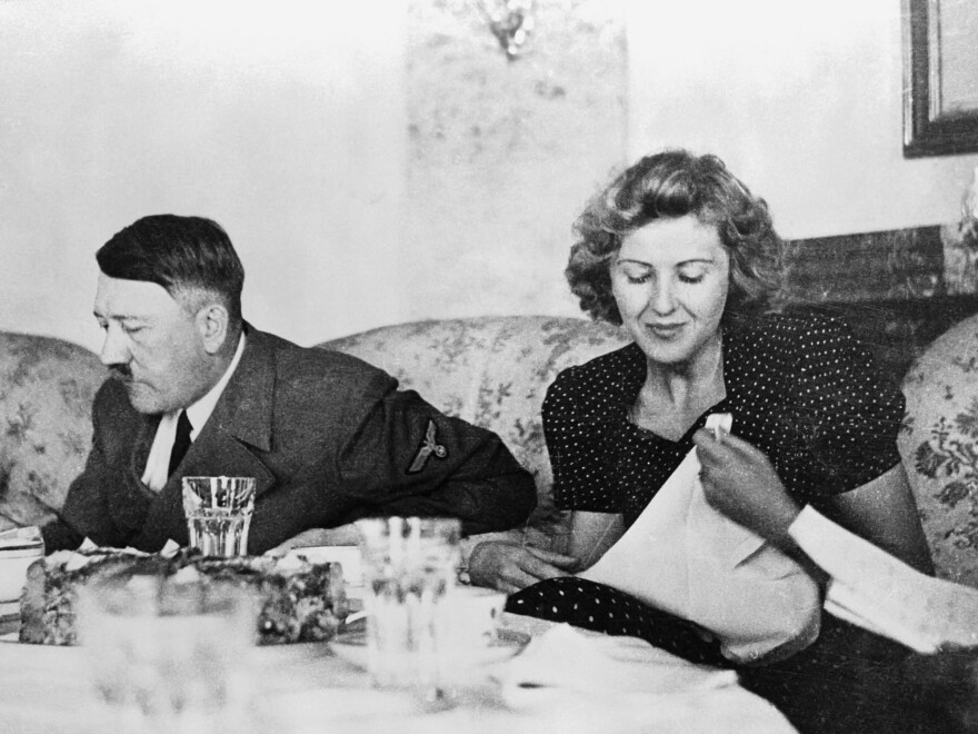 """Berlin, Germany: A candid photograph of Eva Braun with Adolf Hitler at the dining table. A new book explores the lives of six women through food, and Hitler's mistress is a startling inclusion. But what Braun ate reflected a """"perpetual enactment of her own daydream"""" against a barbaric backdrop."""