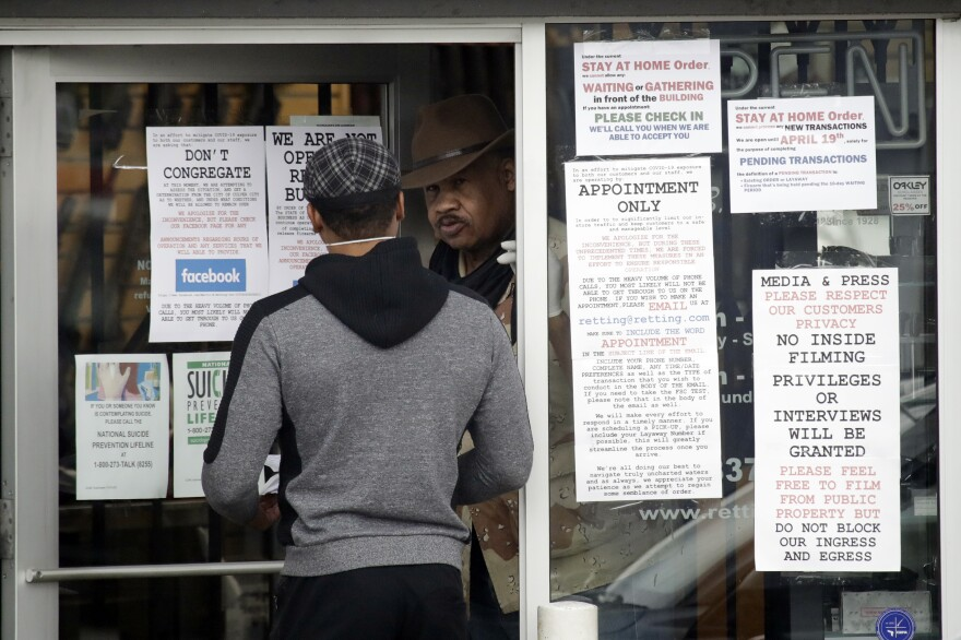 An employee answers questions at the entrance to a gun shop Tuesday in Culver City, Calif.
