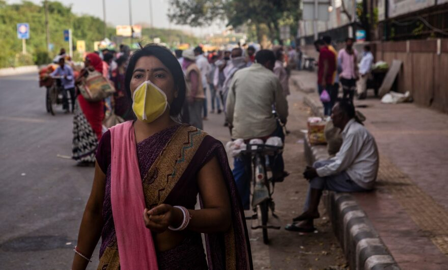 A woman covers her face with a mask as she walks in a crowded New Delhi market place, during India's nationwide lockdown.