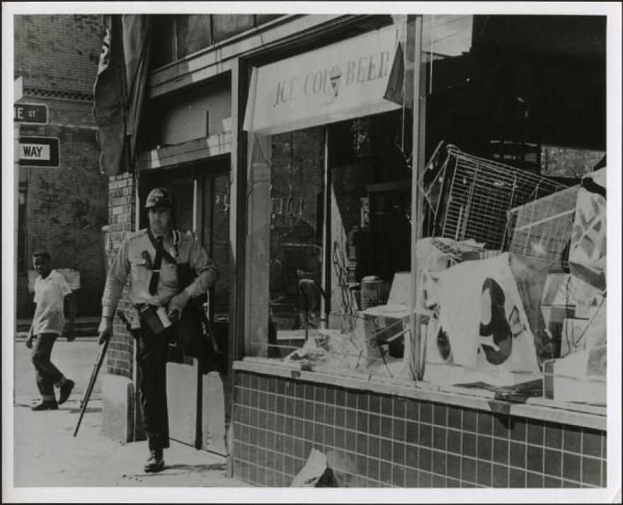 policeman_standing_outside_looted_restaurant.jpg