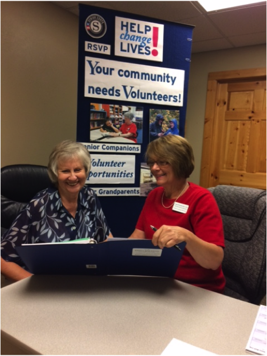 Linda Howard and Carla Schade look through a blue binder together