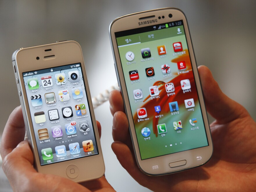 An employee holds Apple's iPhone 4S (left) and Samsung's Galaxy S III at an electronics store in Seoul, South Korea. Some U.S. phone designers are now conflicted over what a recent decision that Samsung infringed on Apple mobile phone patents will mean for their work.