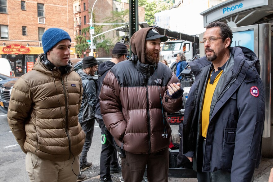 Benny (left) and Josh Safdie stand with Adam Sandler while filming <em>Uncut Gems</em>.
