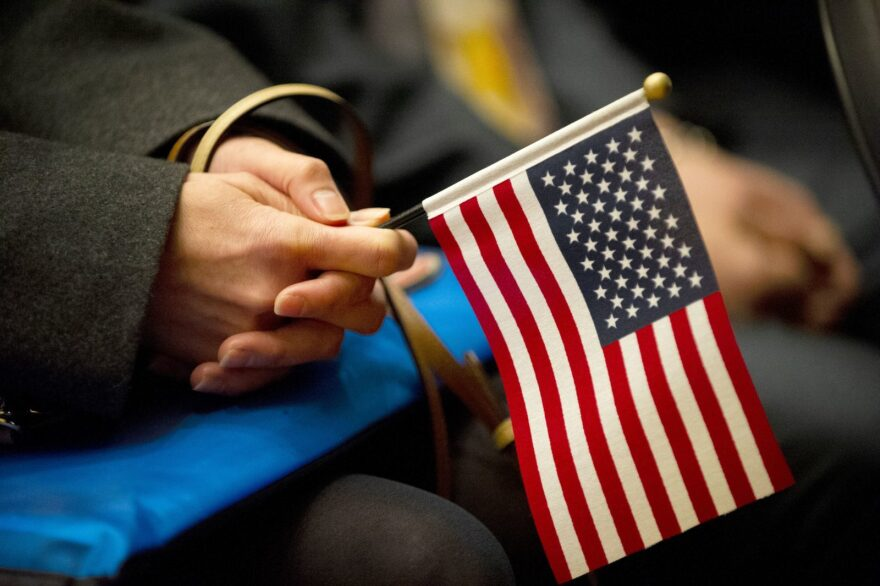 A woman holds a American flag during a naturalization ceremony.