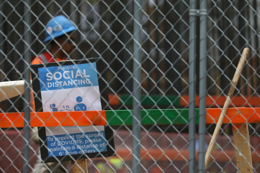 A sign encourages construction workers in Austin to social distance.