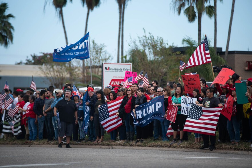 Crowd standing along a street holding American flags and banners and signs supporting Donald Trump.