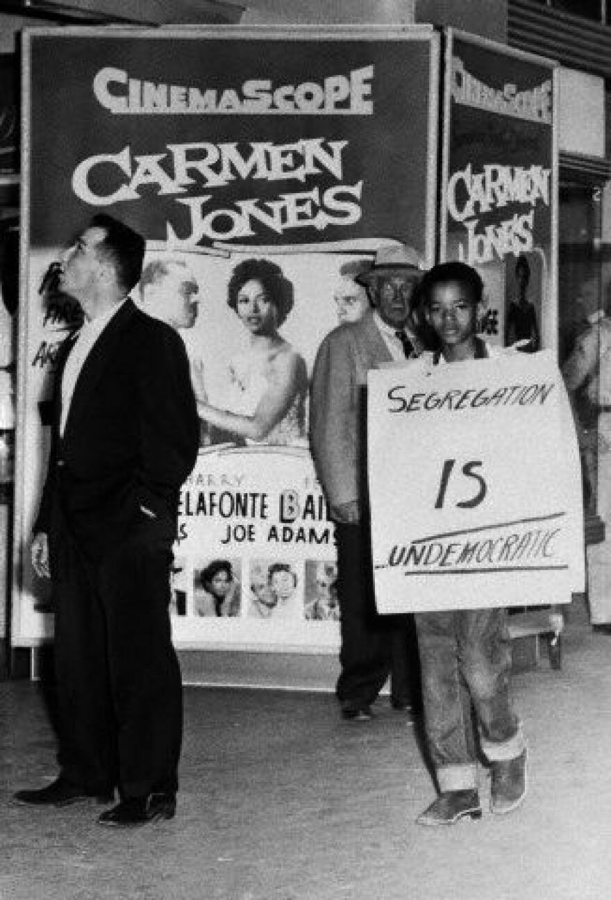 """Alfred S. James, president of the city's NAACP youth committee, protests the segregation policy at a San Antonio movie house during a showing of """"Carmen Jones."""""""
