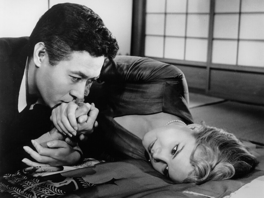 Hidenari Terasaki (James Shigeta) kisses the hand of his wife, Gwen (Carroll Baker), in the 1961 film <em>Bridge to the Sun</em>.