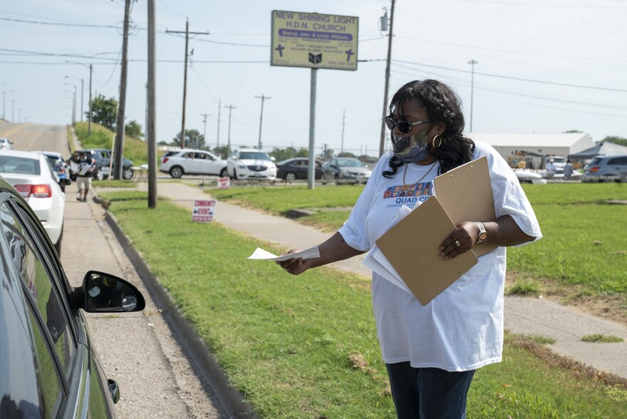 Dewanda Crochrell hands out instructions to a resident detailing how to respond to the 2020 census in Venice, Ill. on Aug. 29. Crochrell works with the Quad City Community Development Center to boost the census response rates in Madison County.