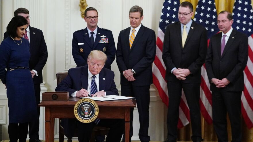 President Trump, surrounded by federal officials on Thursday, signs a proclamation for Older Americans Month during an event on protecting seniors from the coronavirus.