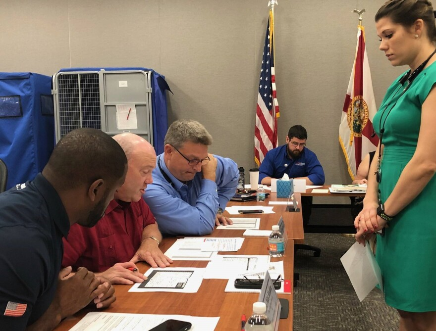 Leon County Supervisor of Elections Mark Earley, Judge Layne Smith and County Commissioner Nick Maddox review signatures on mail-in ballots.