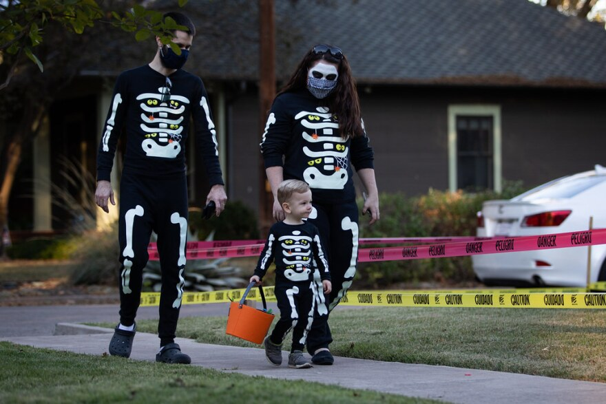 Dressed as skeletons, David and Jaime Brown take their 2-year-old son, Houston, trick-or-treating in the Hyde Park neighborhood.