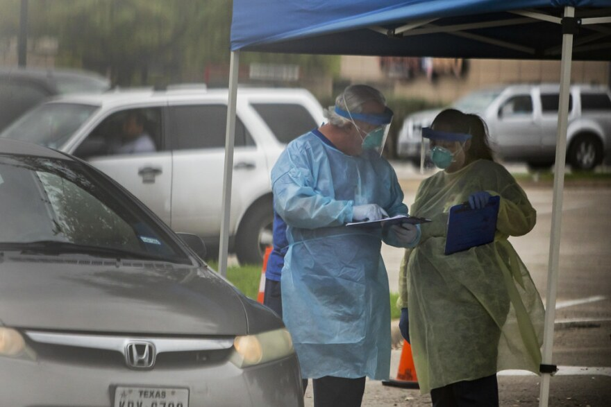 Workers handle paperwork at a drive-thru coronavirus screening site at CommUNITYCare Clinic at the Hancock Center in Austin last month.