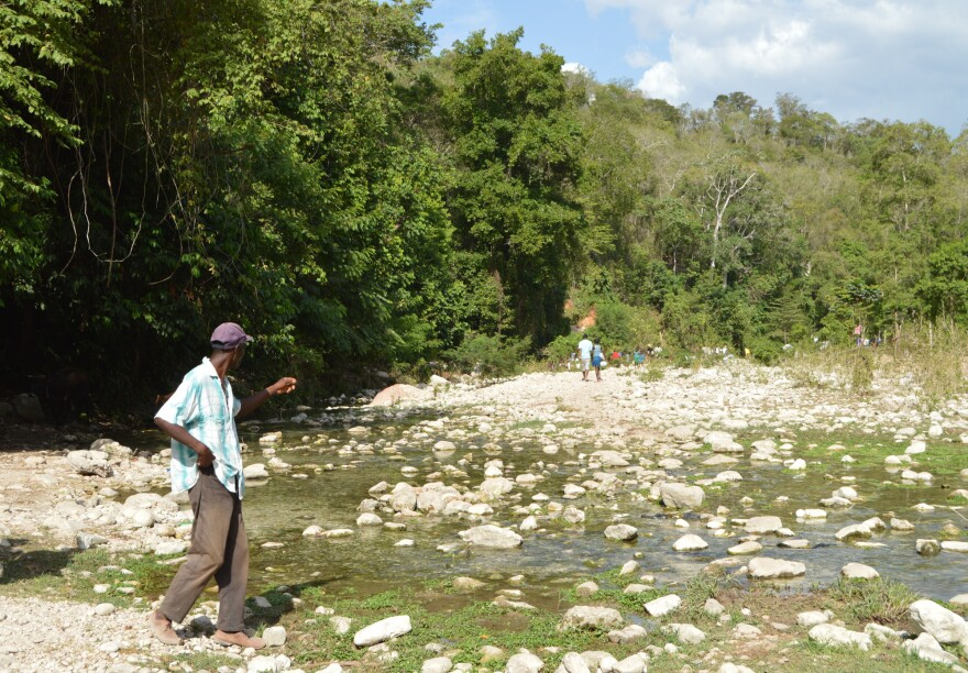 Jean Louis Andres walks in the river that separates Haiti and the Dominican Republic.