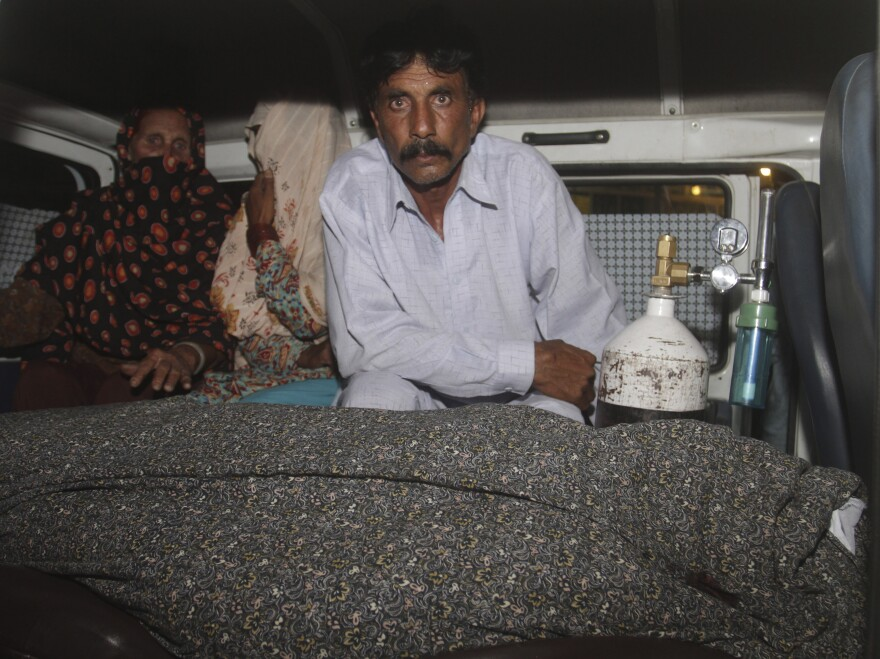 Mohammad Iqbal, husband of Farzana, sits in an ambulance next to the body of his pregnant wife, who was stoned to death by her own family in Lahore, Pakistan, on Tuesday.
