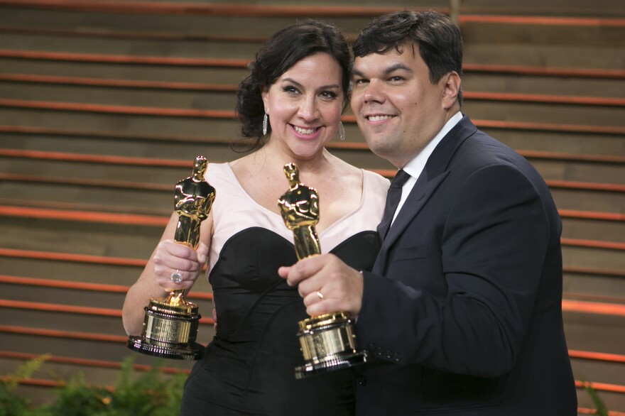 Kristen Anderson-Lopez and Robert Lopez arrive with their Academy Awards for best original song to the 2014 Vanity Fair Oscar Party in West Hollywood.