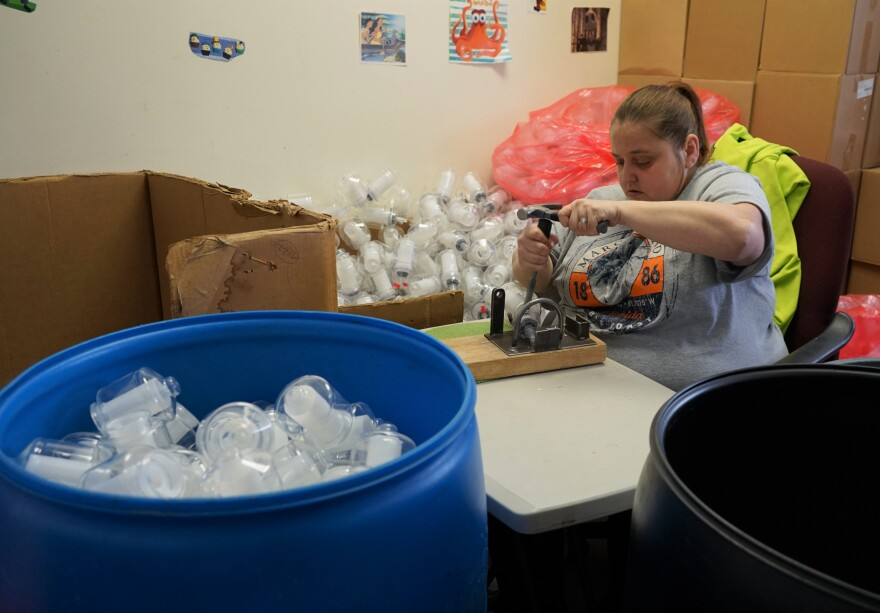 Photo of worker sorting bottles.