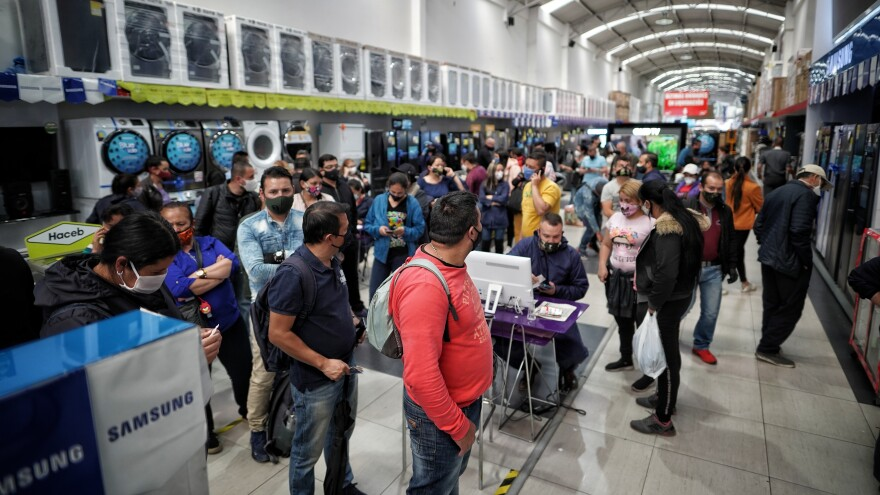Shoppers browse at an electronics store in Bogotá, Colombia, on June 19. Shoppers flocked to Colombian shopping malls to take advantage of a day without value added tax, which triggered Black Friday-style shopping frenzies.