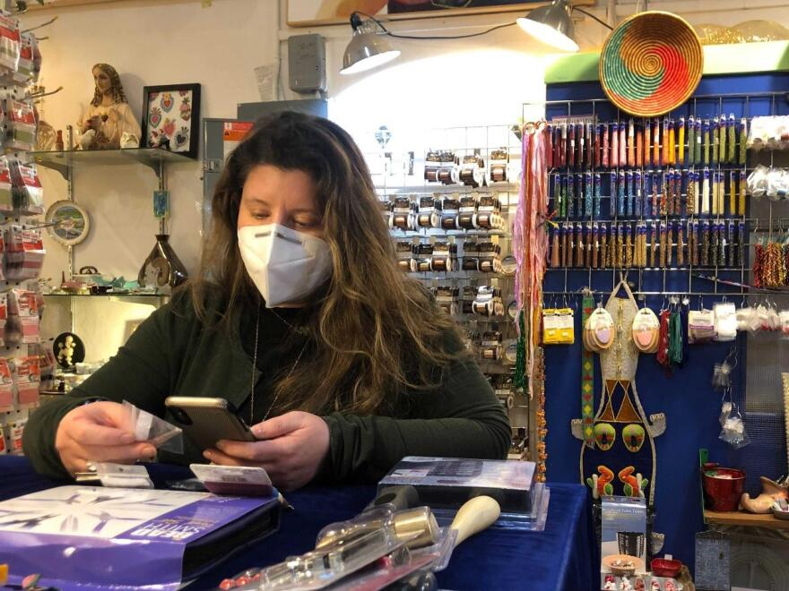 Katie Ghen Simpson makes a sale over FaceTime on December 16, 2020 at Bathing Beauties Beads, where she is the owner.