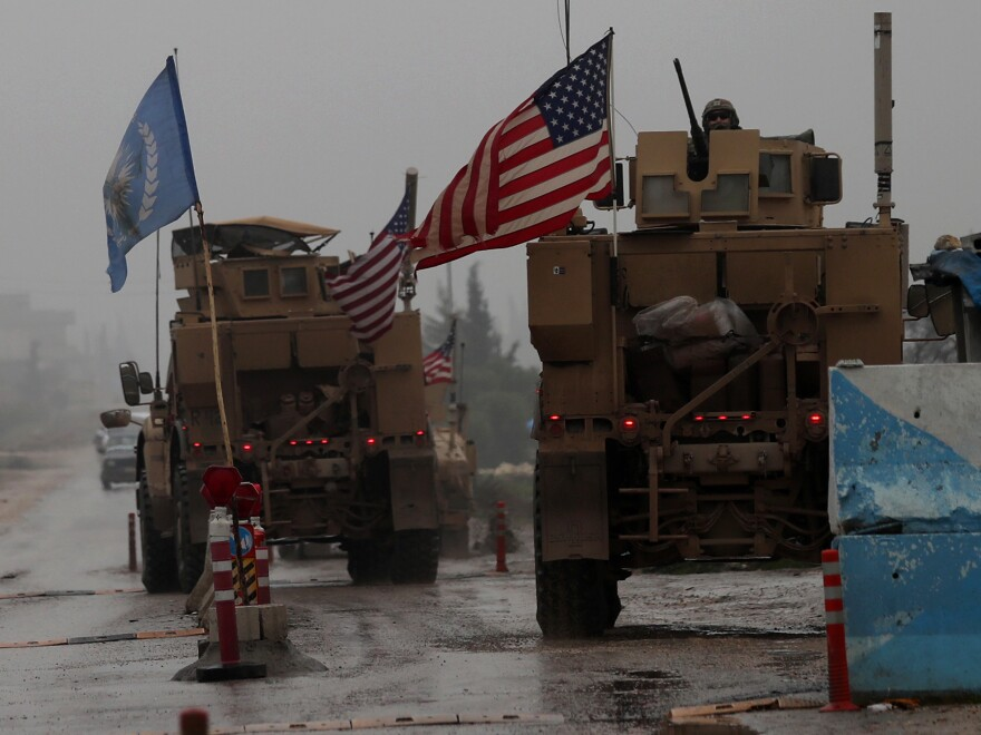 """The Pentagon has """"begun the process of our deliberate withdrawal from Syria,"""" a military spokesman says. In this photo from Dec. 30, 2018, a line of U.S. military vehicles are seen at a checkpoint in northern Syria."""
