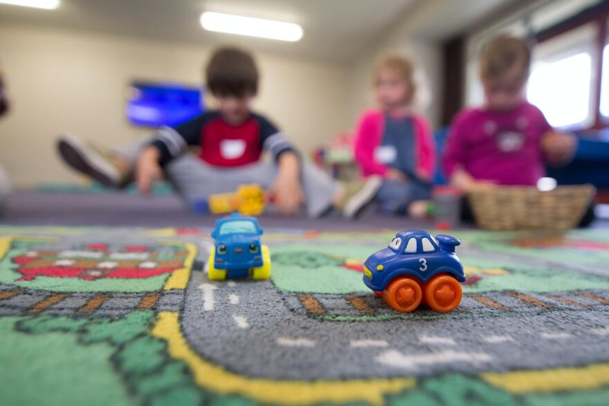 A photo of children at a daycare, with the focus on toy cars.