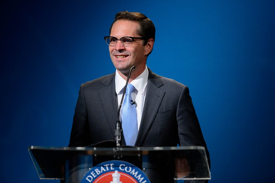 A man with glasses in a suit with a blue tie stands smiling at a podium.