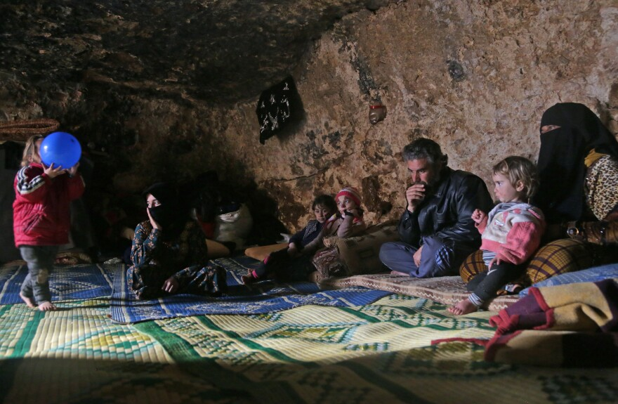 Members of a family of internally displaced Syrians sit in an underground shelter in Idlib province on Sunday.