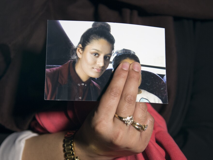The eldest sister of Shamima Begum holds her sister's photo in 2015. Begum, who left London to join the Islamic State as a teenager, is now trying to return to the U.K. to argue her British citizenship should not be revoked.
