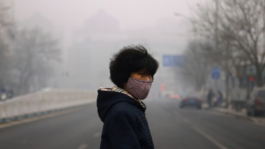 A woman wearing face protection walks across a street during a hazy day in Beijing on March 27. Worsening air pollution is fueling a slow exodus of expatriates from the Chinese capital.