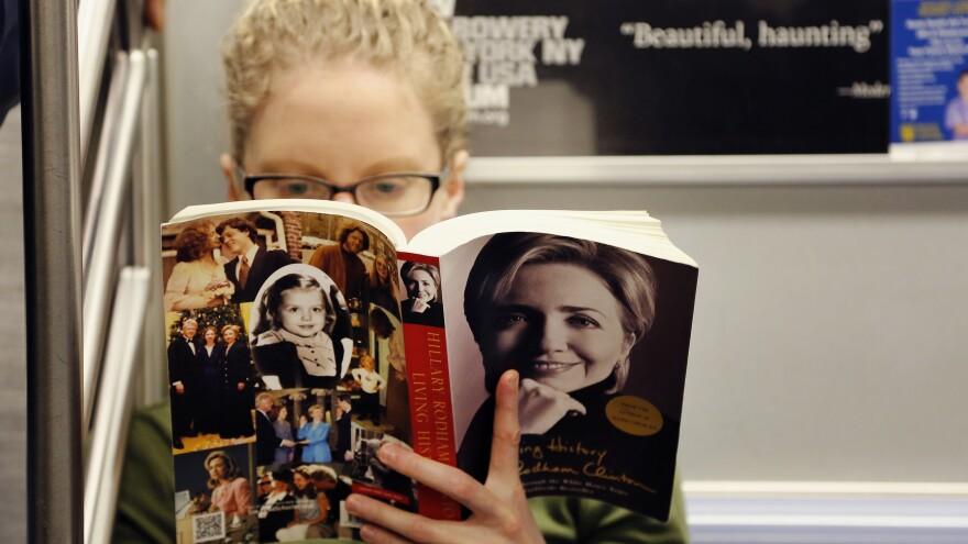 Linda Leseman reads Hillary Clinton's memoir, <em>Living History</em>, while riding the New York City subway Tuesday.