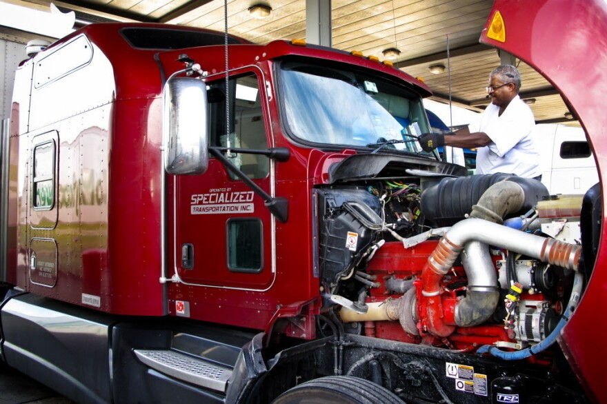"""Errol Giwa, en route to Washington, D.C., fuels up and wipes down his windshield at the truck stop in Jessup, Md. He says in his 34 years as a truck driver, he has heard of many instances of human trafficking at truck stops but hasn't seen it with his own eyes. """"If you are looking for that sort of thing, it's not hard to find on the road,"""" Giwa says."""