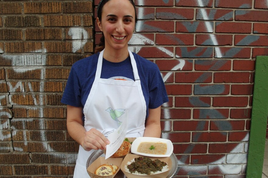 Mana Heshmati, founder of the Detroit-based Peace Meal Kitchen, stands outside of the Detroit City Distillery in Eastern Market during a fundraising event for the ACLU of Michigan. Within two hours, she sold out of her a la carte menu, which included <em>ghormeh sabzi, </em>a Persian beef stew, a vegetarian cream of barley soup, and <em>shirini keshmeshi</em>, delicate rosewater raisin cookies.