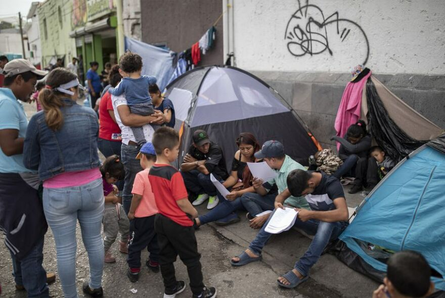 Migrants look over their documents at a makeshift migrant camp at the base of the Paso del Norte International Bridge in Ciudad Juárez on Oct. 3. Migrants wait close to the port of entry so they won't lose their spot in line to legally cross into the U.S.