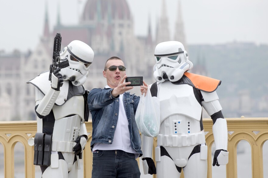 In Budapest, Hungary, a man takes a photo with people dressed as their favorite <em>Star Wars</em> stormtroopers.