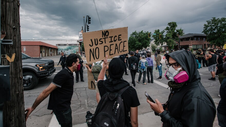 Photo of a man holding a sign that reads 'no justice no peace'.