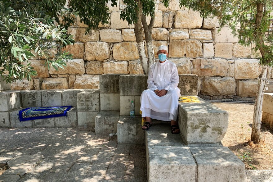 Mustafa Abu Sway, on the Al-Aqsa Mosque advisory council, sits outside the mosque next to his yellow carpet. Worshipers are asked to bring their own prayer carpets from home now. Abu Sway says he's never laundered so many carpets in his life.